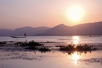 Pêcheur intha sur fond de couché de soleil sur le lac Inlé